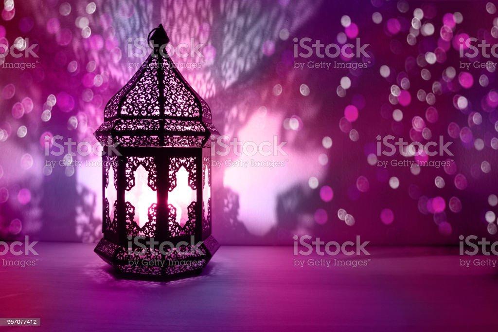 Ornement lanterne arabe avec combustion bougie allumé pendant la nuit et scintillants de lumières colorées bokeh. Carte de voeux Fête, invitation pour le mois sacré musulman Ramadan Kareem. Une partie floue de fond - Photo