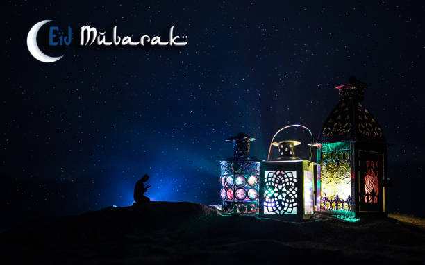 ornamental arabic lantern with burning candle glowing at night. festive greeting card, invitation for muslim holy month ramadan kareem. - eid stock pictures, royalty-free photos & images