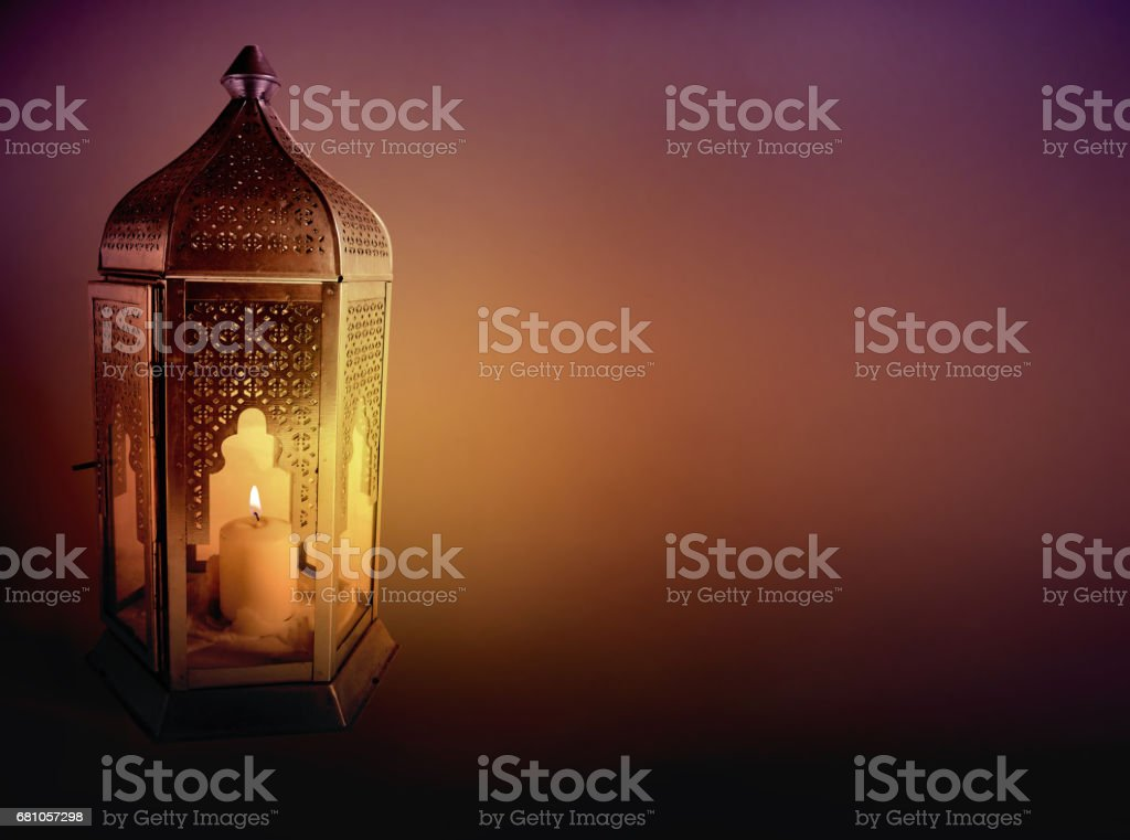 Ornamental Arabic lantern with burning candle glowing at night. Greeting card, invitation for Muslim community holy month Ramadan Kareem. Dark background with a lot of empty space. stock photo