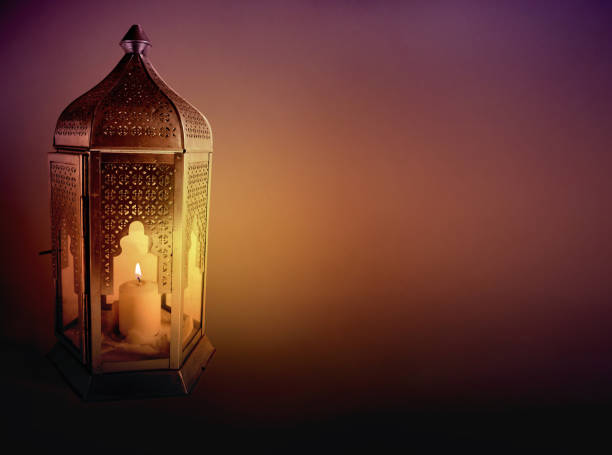 ornamental arabic lantern with burning candle glowing at night. greeting card, invitation for muslim community holy month ramadan kareem. dark background with a lot of empty space. - eid stock pictures, royalty-free photos & images