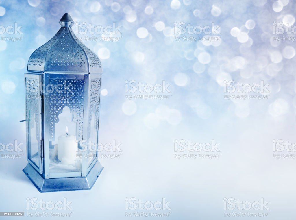 Ornamental Arabic lantern with burning candle glowing at night. Greeting card, invitation for Muslim community holy month Ramadan Kareem. Glittering festive blue background with bokeh lights. stock photo