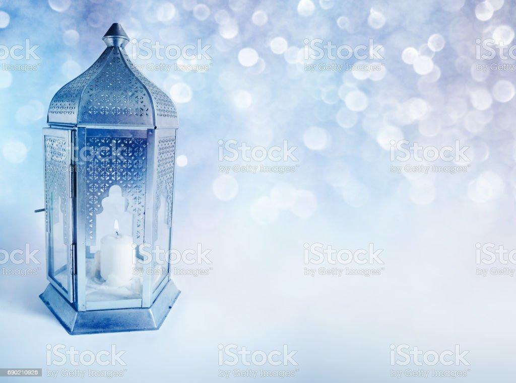 Lanterna árabe ornamental com vela queima a brilhar à noite. Cartão de felicitações, convite para o mês sagrado da comunidade muçulmana Ramadan Kareem. Fundo azul festivo brilhante com luzes de bokeh. - foto de acervo