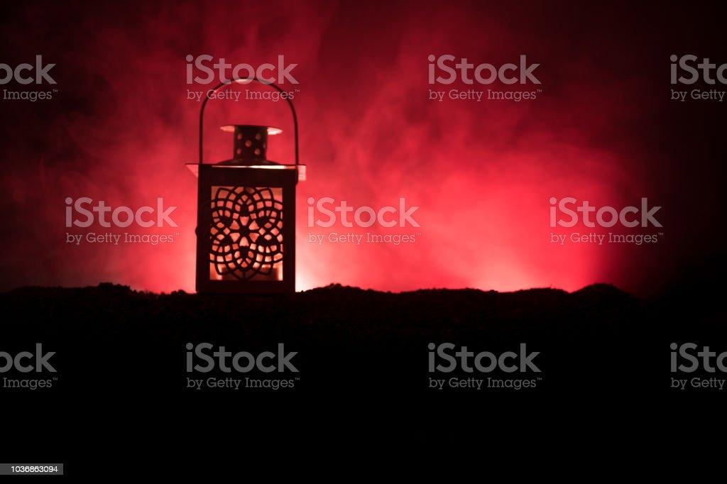 Ornamental Arabic lantern with burning candle glowing at night on dark toned foggy background. Festive greeting card, invitation for Muslim holy month Ramadan Kareem. stock photo
