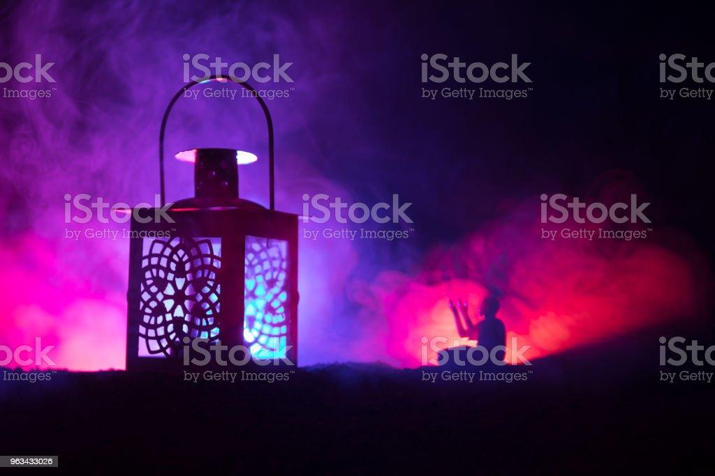 Prydnads arabiska lykta med brinnande ljus glödande nattetid på mörk tonad dimmig bakgrund. Festlig gratulationskort, inbjudan för muslimska heliga månaden Ramadan Kareem. - Royaltyfri Affisch Bildbanksbilder