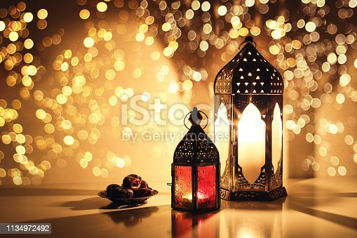 istock Ornamental Arabic lanterns with burning candles. Glittering golden bokeh lights. Plate with date fruit on the table. Greeting card for Muslim holiday Ramadan Kareem. Iftar dinner background. 1134972492