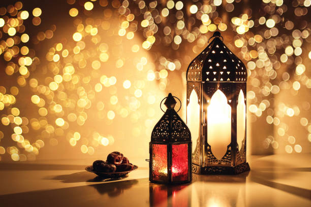 ornamental arabic lanterns with burning candles. glittering golden bokeh lights. plate with date fruit on the table. greeting card for muslim holiday ramadan kareem. iftar dinner background. - eid stock pictures, royalty-free photos & images