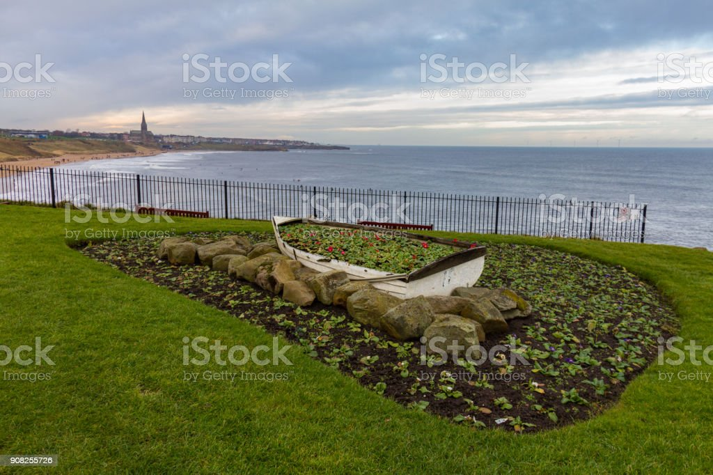 Ornamental Boat containing Flowers, with Tynemouth's Coastline in the background stock photo