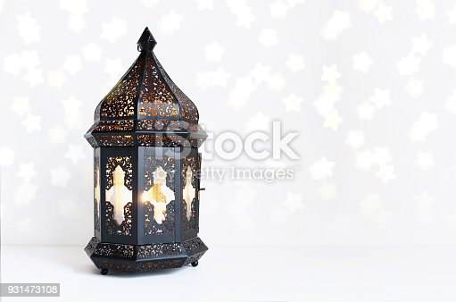 istock Ornamental dark Moroccan, Arabic lantern on the white table. Burning candle, glittering bokeh lights stars. Greeting card for Muslim community holy month Ramadan Kareem. Festive background 931473108