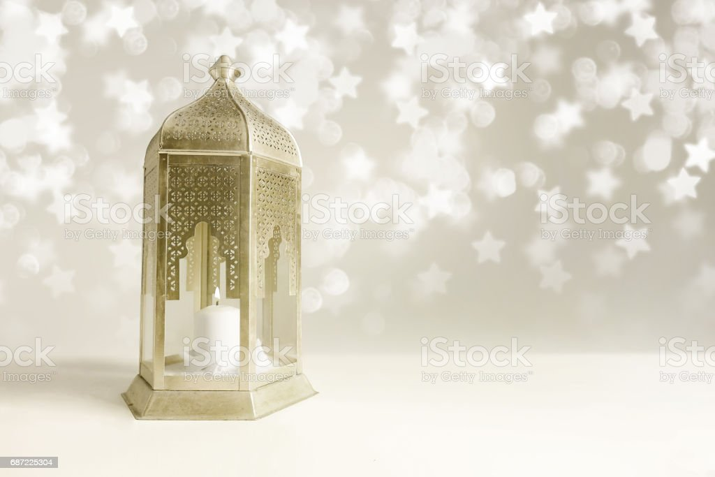 Ornamental golden Arabic lantern on the table with glittering star-shaped bokeh lights. Greeting card for Muslim community holy month Ramadan Kareem. Festive blurred background with empty space stock photo