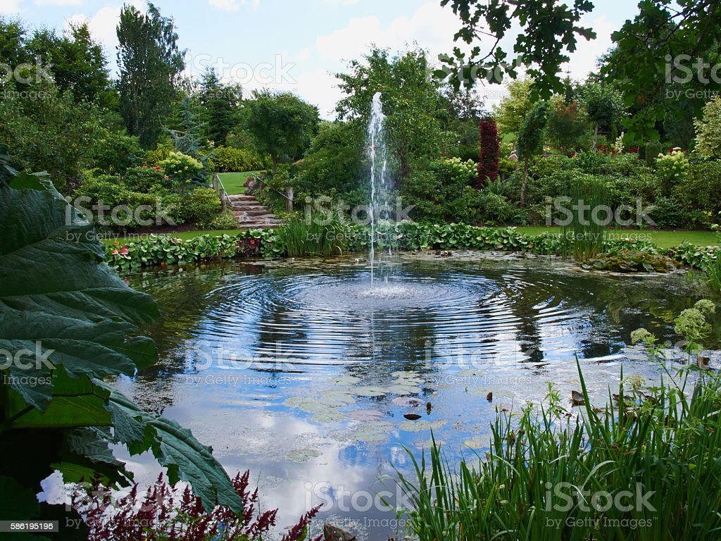 Ornamental pond and water fountain in a garden stock photo