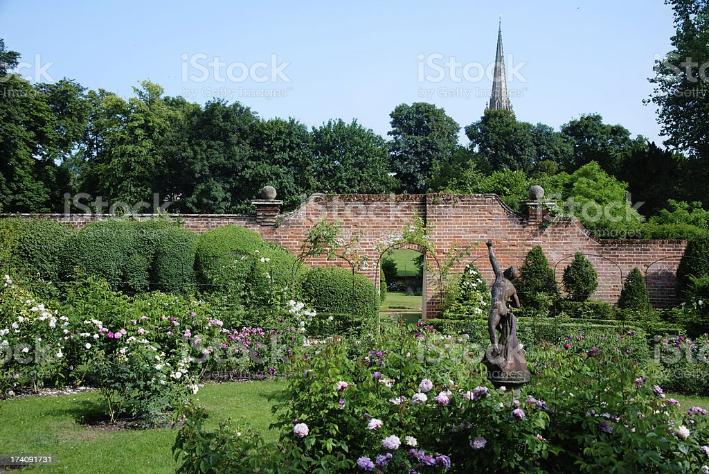 Ornamental Rose Garden with old statue wall and church stock photo