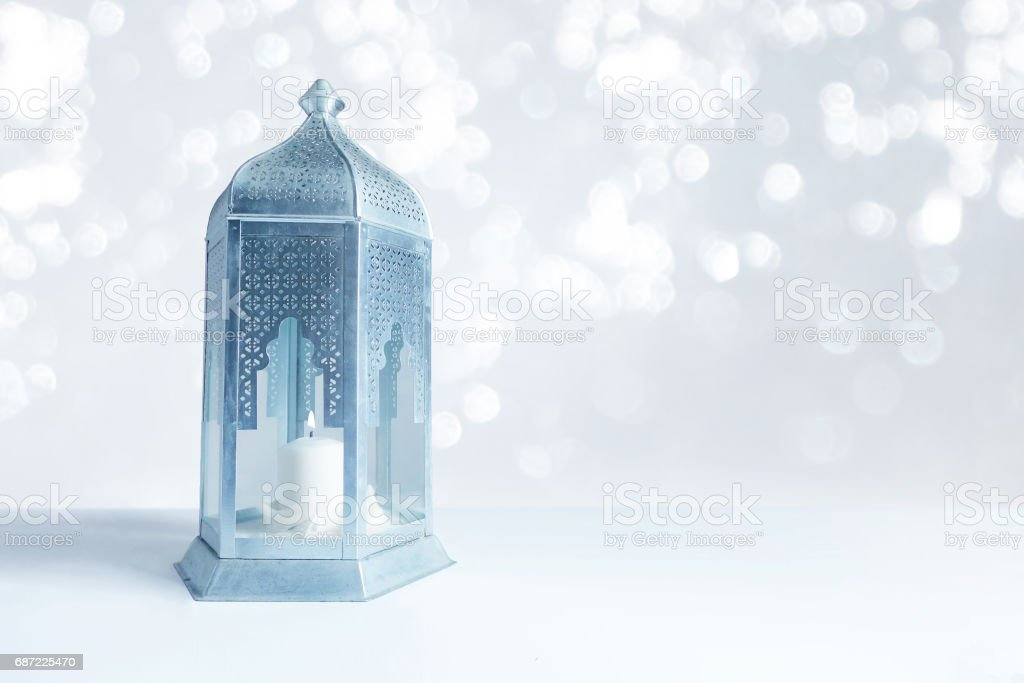Ornamental silver and blue Arabic lantern on the table with glittering bokeh lights. Greeting card for Muslim community holy month Ramadan Kareem. Festive blurred background with a lot of empty space stock photo