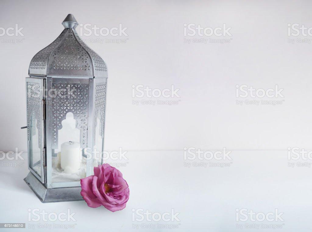 Ornementale lanterne arabe argentée avec fleur rose sur la table. Carte de voeux Ramadan, invitation. - Photo