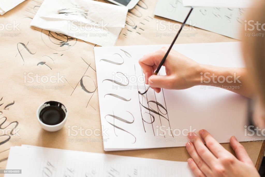 ornamentation, graphic design, education concept. woman preparing writing exercises for learning calligraphy. there is different types of lines and capital letters of russian alphabeth stock photo