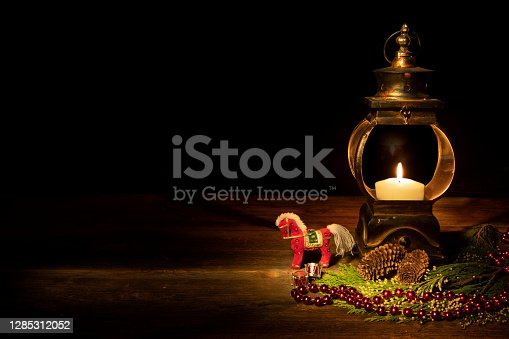 A Western holiday theme with ornate lit candle lantern against black background for reverse text