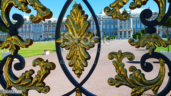 Pushkin, St. Petersburg, Russia - June 23, 2019: Ornate elements of Golden Gate of Catherine Palace in Pushkin, suburb of St. Petersburg, Russia. Wrought iron ancient fence after renovation. Historical architecture. Gold plated decorative details.