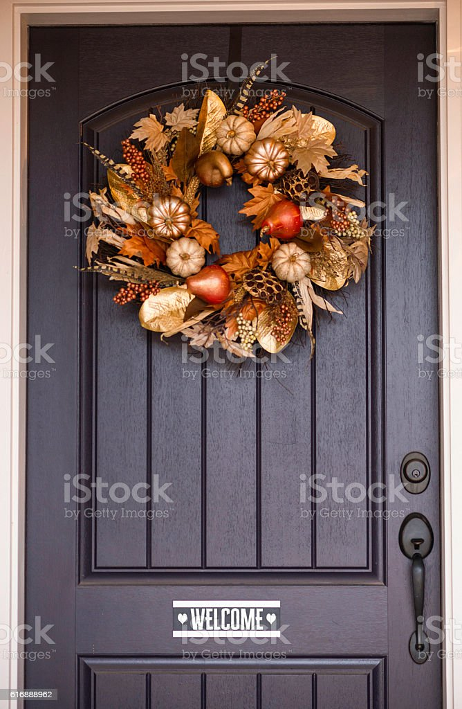 Ornate fall wreath with gold pumpkins hanging on front door bildbanksfoto