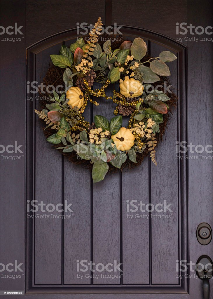 Ornate fall wreath with white pumpkins hanging on front door stock photo