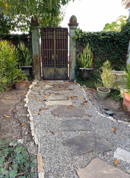 Ornate garden gate with stone path. stock photo