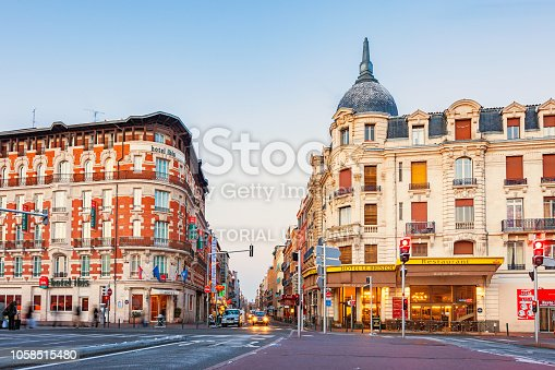Pedestrians and car move below ornate hotels at the main railway station, in downtown Toulouse, France on a clear morning.