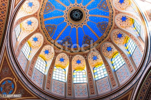 Wide angle color image depicting the ornate decorative architecture inside a Jewish synagogue. The dome and stained glass windows are adorned with an elaborate pattern using the star of David symbol. Room for copy space.