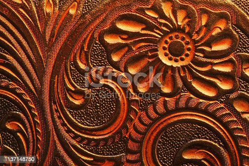 A tooled leather surface that displays a classic western style design.