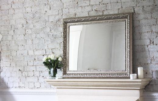 An antique mirror on a mantlepiece