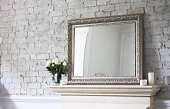 An antique mirror on a mantlepiece