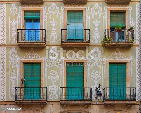 istock Ornate painted building facade and windows with green wooden shutters in the Gothic Quarter in Barcelona, Spain 1078306578