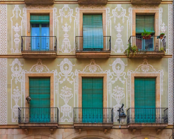 Ornate painted building facade and windows with green wooden shutters in the Gothic Quarter in Barcelona, Spain stock photo