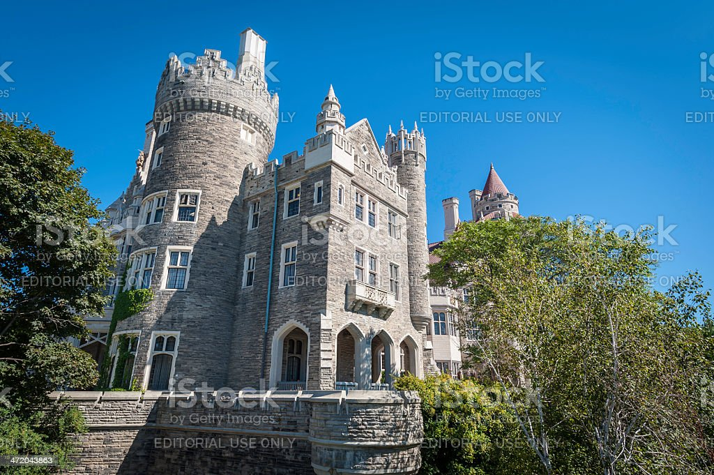 Ornate period castle home with towers under clear blue skies stock photo