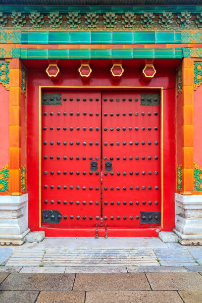 Ornate red wooden door with tile trim and traditional Chinise design in Forbidden City In Beijing China Ornate red wooden door with tile trim and traditional Chinise design at the Forbidden City, In Beijing, China forbidden city stock pictures, royalty-free photos & images