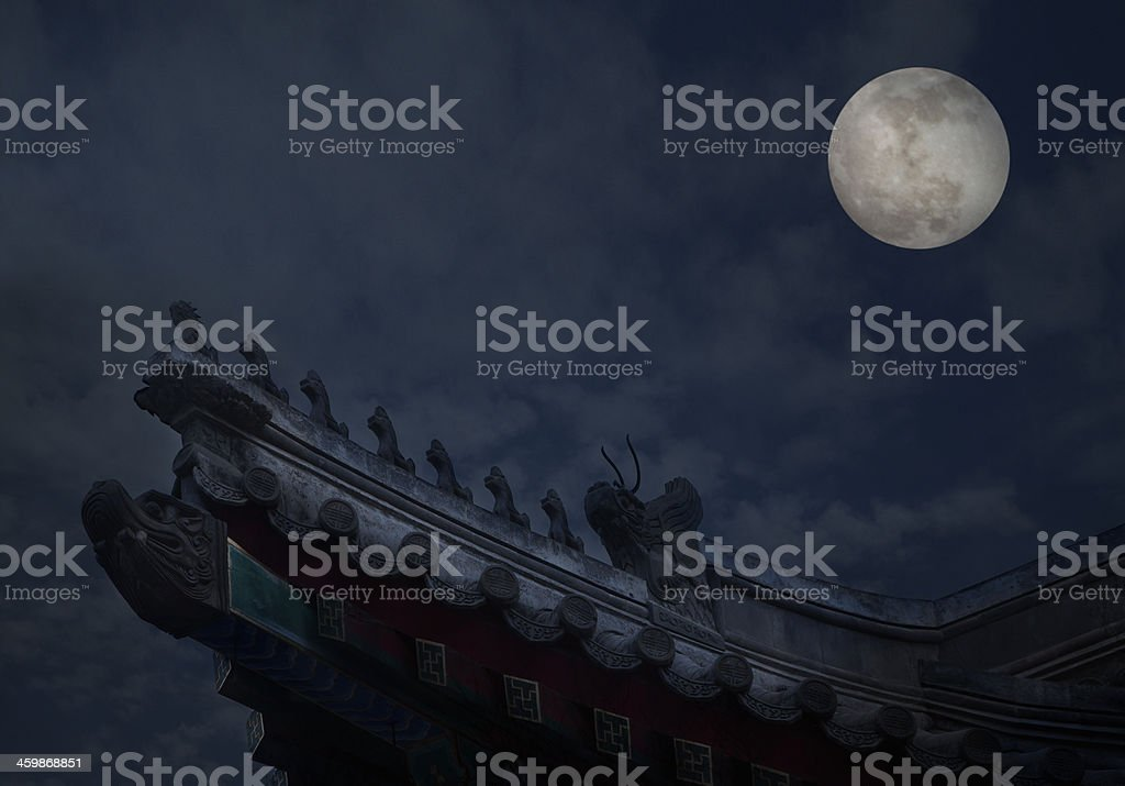 Ornate roof tiles on Chinese building with moon background, night. royalty-free stock photo