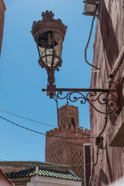Ornate street lamp with a mosque minaret behind in Marrakesh stock photo