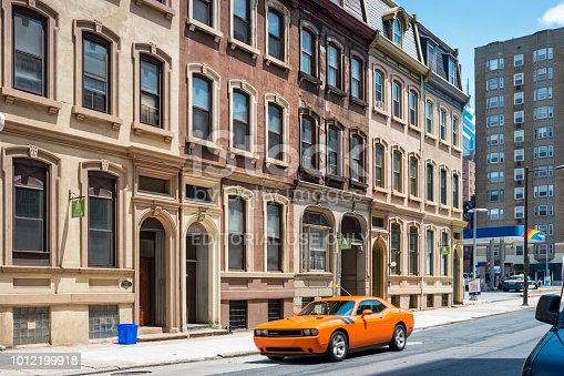 Dodge Challenger moves past ornate townhomes on Walnut Street in downtown Philadelphia, Pennsylvania, USA on a sunny day.