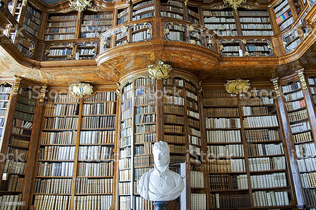 Ornate two story wall of book shelves and a white bust royalty-free stock photo