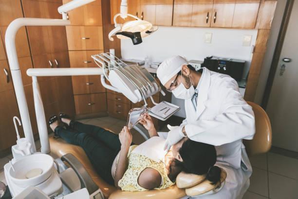 Kieferorthopäde behandelnde junge Frau auf die Zähne in Zahnklinik – Foto