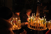 Pskov, Russia - January 18, 2011: Orthodox believers light candles during the Epiphany evening service in the Church of Saint Alexander Nevsky in Pskov, Russia.