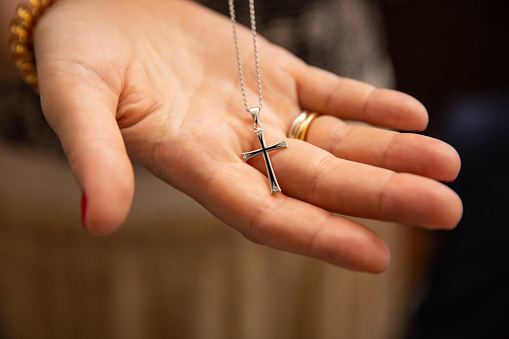 Orthodox christenings of a child, a cross in his father's hand. Macro