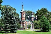 Limbazi, Latvia - Orthodox Church of the Enlightenment of Christ, a building built of burgundy brick with a green roof and black domes, next to a green lawn, trees and Christmas trees, blue sky.