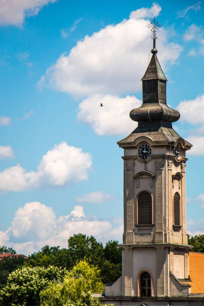 Orthodox church tower with clock under blue sky with clouds and flying bird stock photo