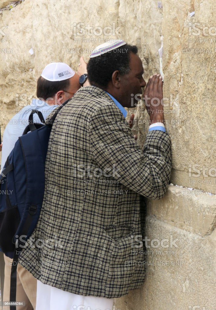 orthodox jewish men, one african one european, praying at the wailing wall in jerusalem, israel, March 8, 2018 royalty-free stock photo