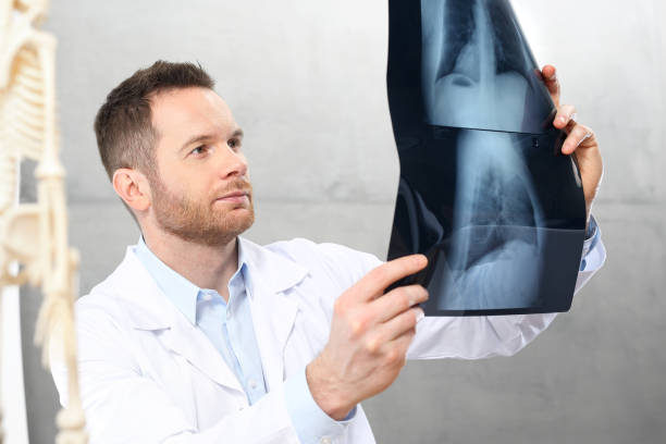Orthopaedist A doctor in a doctor's office is watching an x-ray of a patient. scientific imaging technique stock pictures, royalty-free photos & images