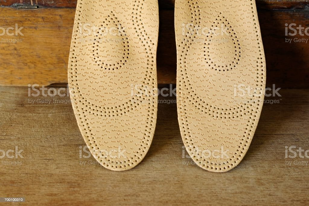 Orthopedic arch support made from leather on a wooden ground stock photo