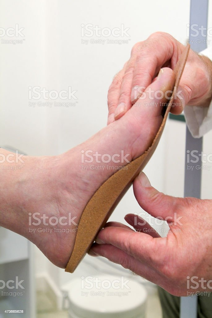 Orthopedic doctor measuring the feet of patient for insoles stock photo