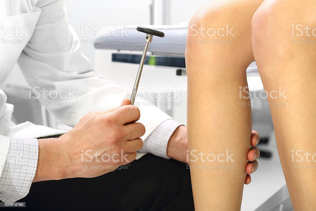 Orthopedic surgeon examining the knee reflex stock photo