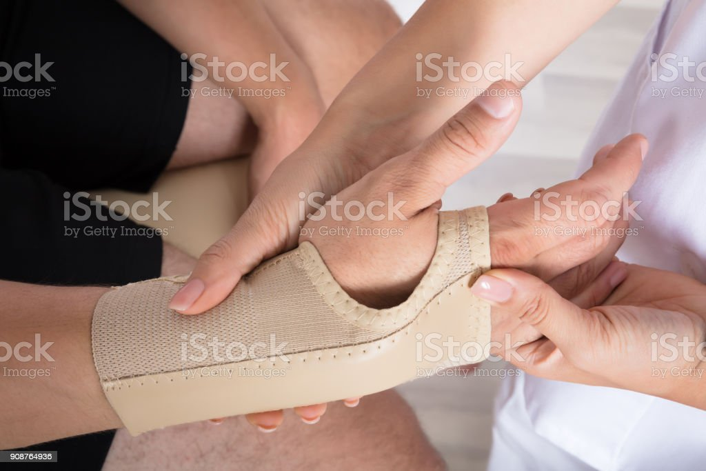 Orthopedist Fixing Plaster On Injured Person's Hand stock photo