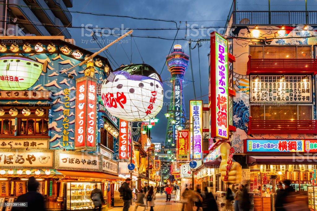 Osaka Shinsekai at Night Tsutenkaku Tower Crowded Shinsekai District, Tsutenkaku Tower in the background. Illuminated Neon Billboards at Night, Vibrant Osaka Shinsekai Cityscape. Shinsekai, Osaka, Japan, Asia Advertisement Stock Photo