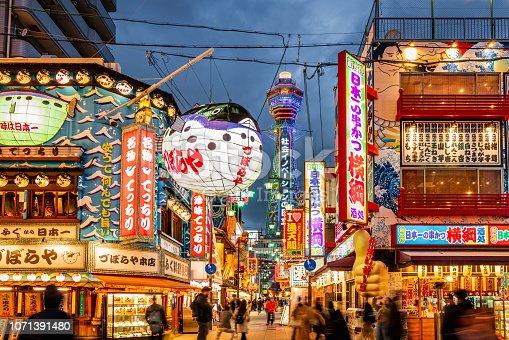 Crowded Shinsekai District, Tsutenkaku Tower in the background. Illuminated Neon Billboards at Night, Vibrant Osaka Shinsekai Cityscape. Shinsekai, Osaka, Japan, Asia