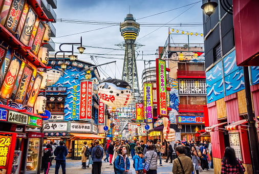 Osaka Tower and view of the neon advertisements in Shinsekai district at dusk, Osaka, Japan